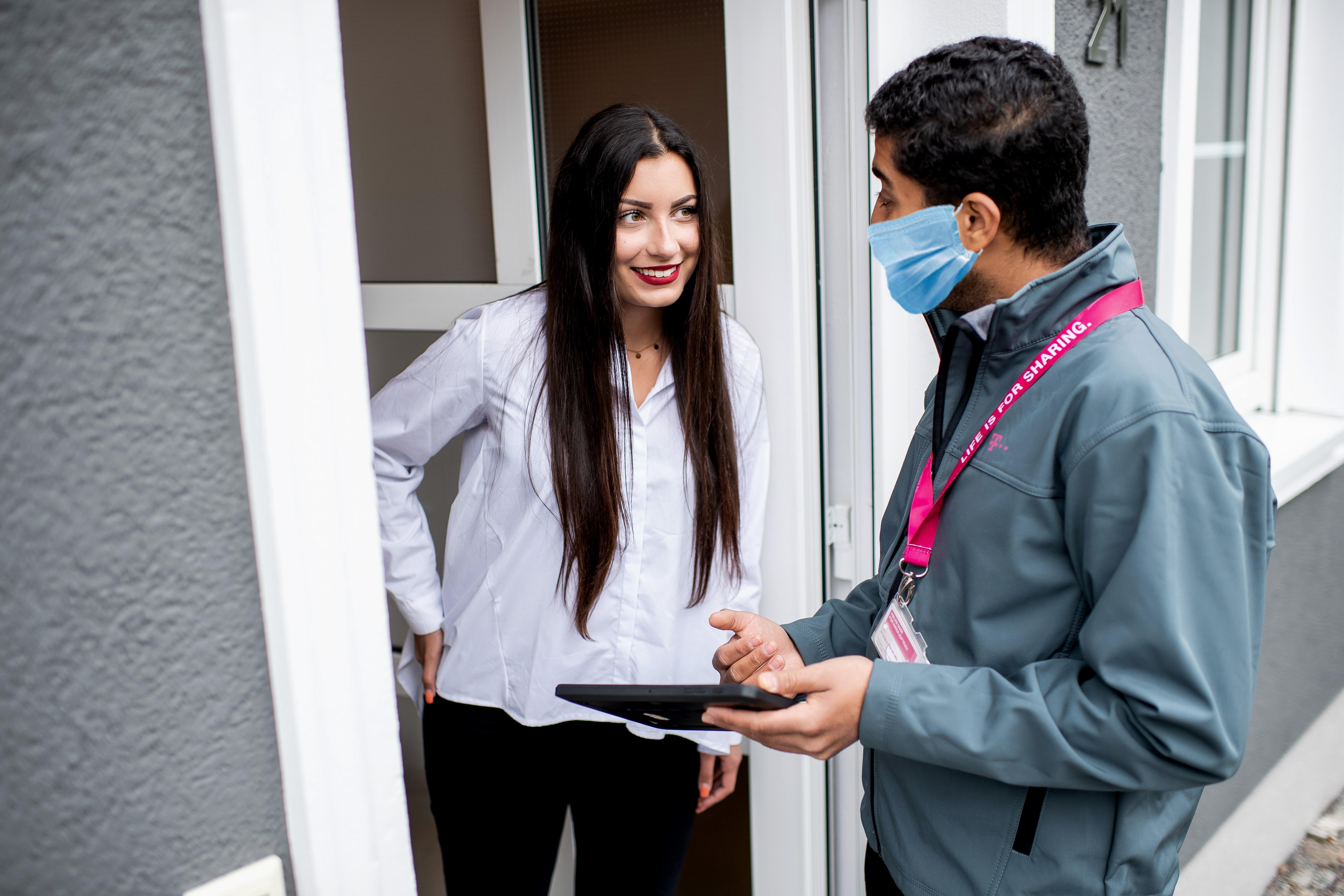 Ein Mitarbeiter der Telekom berät eine potentielle Kundin an der Haustür.