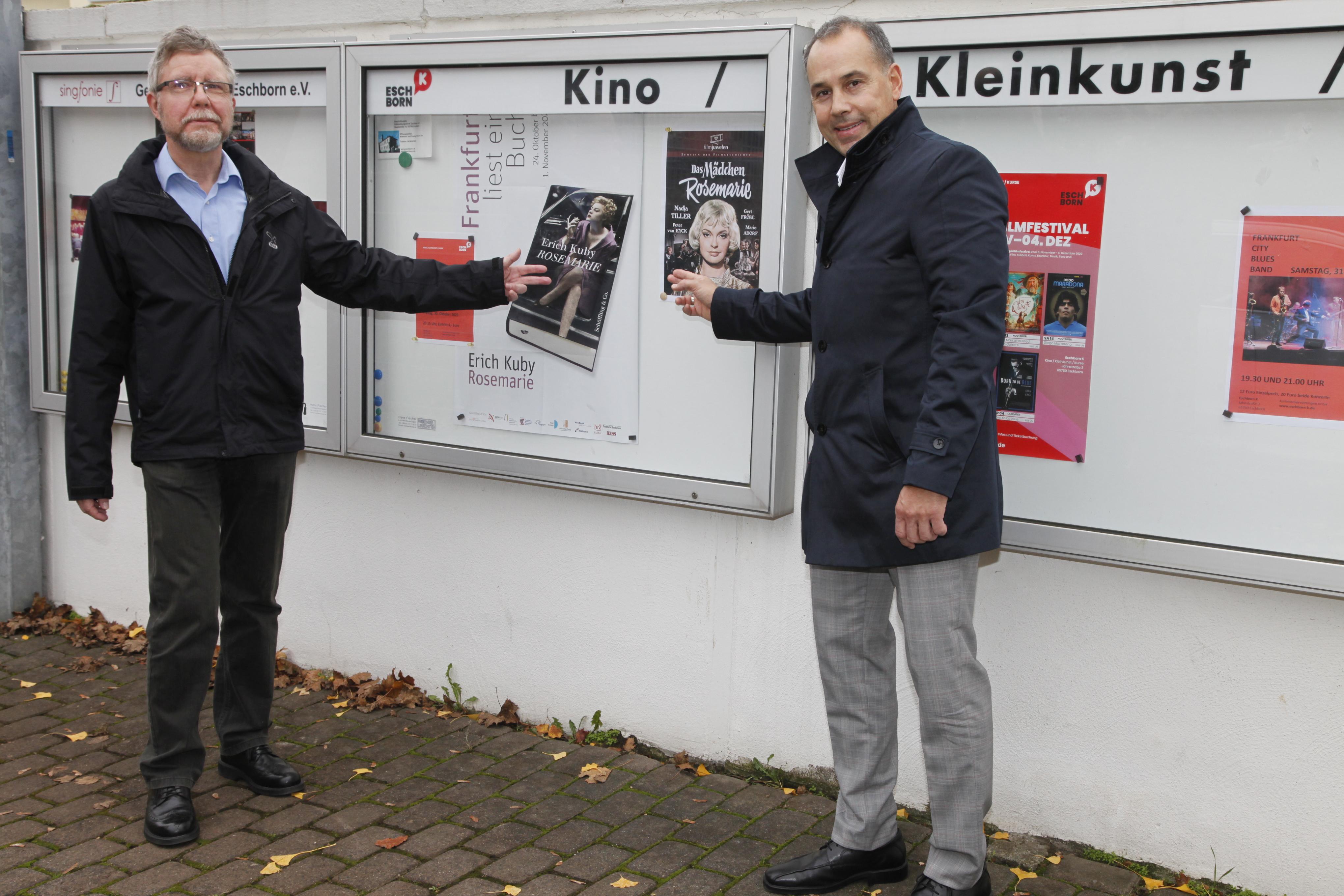 Benno Moritz vom Filmbeirat des Eschborn K mit Bürgermeister Adnan Shaikh (rechts) vor einem Schaukasten des Kinos.