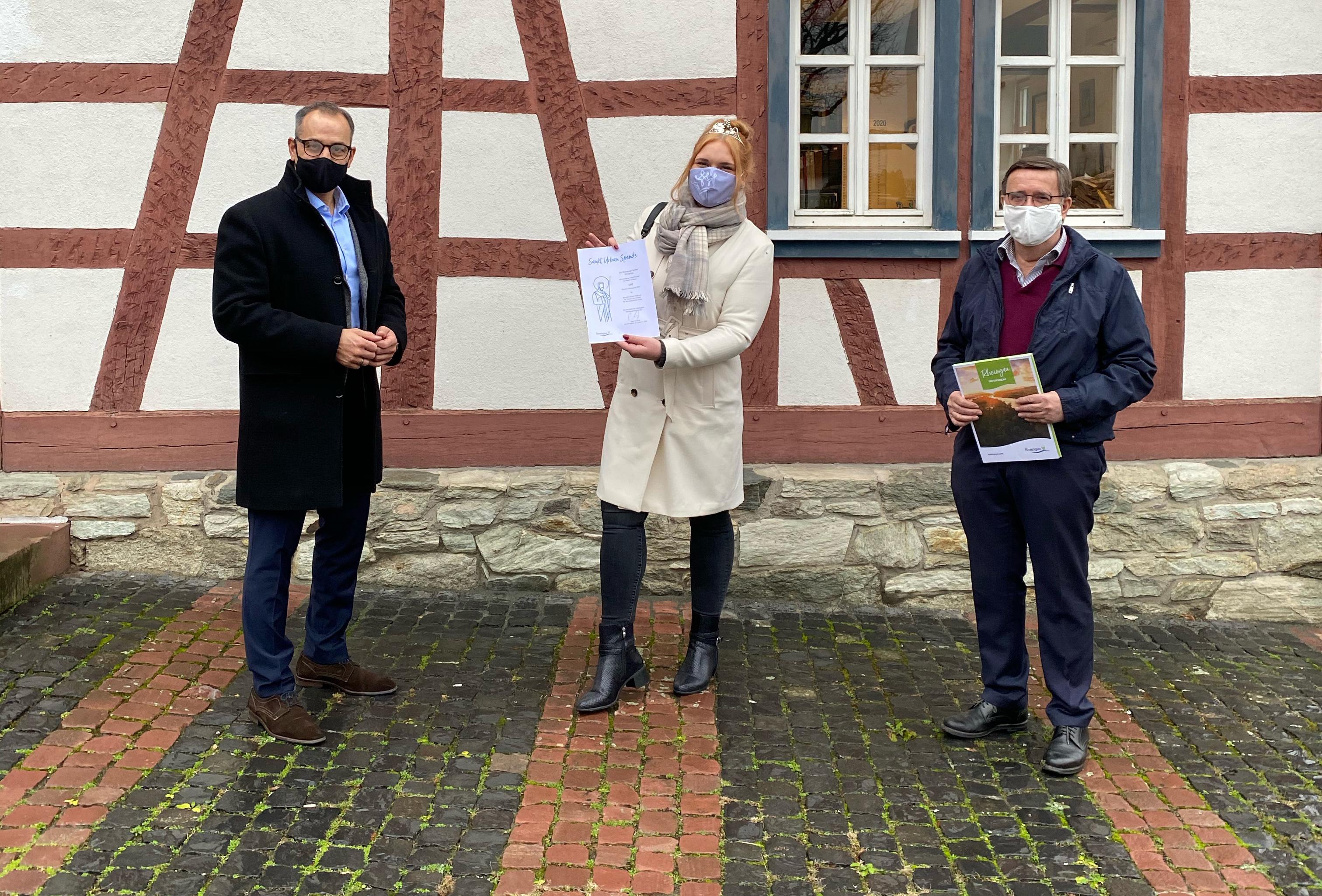 Bürgermeister Shaikh nimmt aus den Händen der Rheingauer Weinprinzessin Annika Walther und des Präsidenten des Rheingauer Weinbauverbands Peter Seyffarth die St. Urban-Spende über 270 Flaschen Rheingauer Wein entgegen.