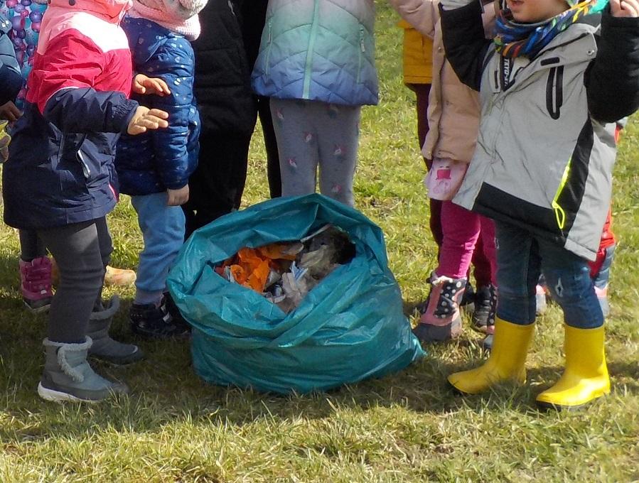 Die Kinder zeigen einen Sack voll mit gesammeltem Müll.